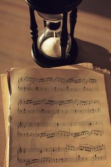 Notes de musique sur papiers et sablier