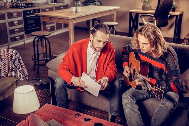 Notes de musique. professeur de musique talentueux aux cheveux noirs barbu montrant ses notes de musique d'étudiant