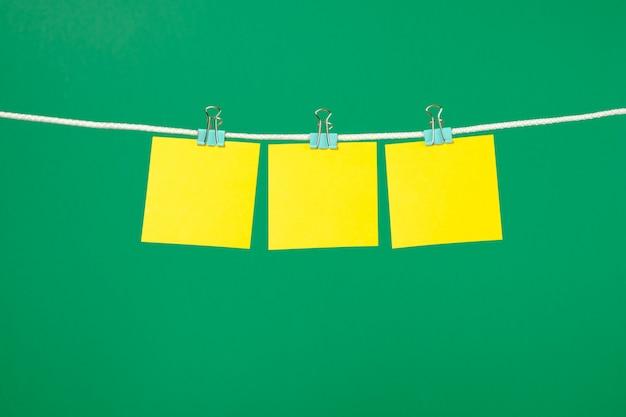 Notes de papier jaune blanc accroché sur une corde à linge