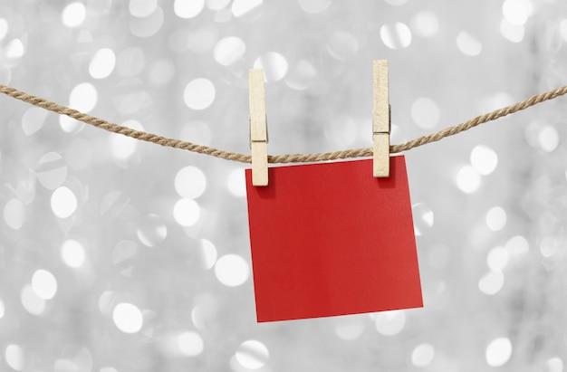 Notes de papier rouge vierge suspendu à une corde à linge.