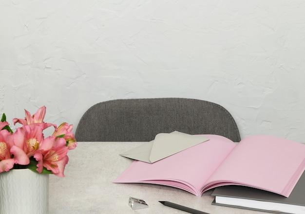 Notes roses, livre, enveloppe, fleurs sur un bureau gris