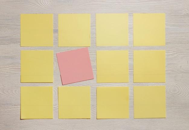 Notes stationnaires, autocollant de couleur vide sur une planche en bois blanche.