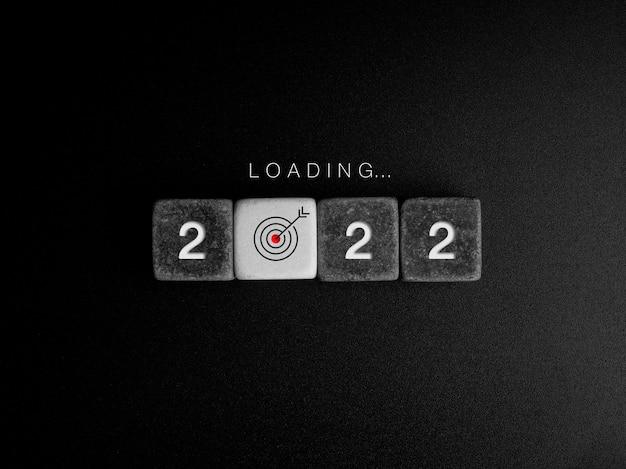 Notion d'année de chargement. numéros de mots et d'année sur des blocs de cubes en noir et blanc avec signe d'icône cible dans la barre de progression dans l'obscurité. mise à jour de l'entreprise, mise à niveau des idées, concepts de pensée créative.
