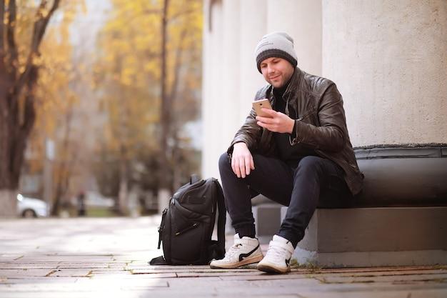 Notion d'automne. un homme se promène dans la ville. feuilles d'automne sur sentier. une