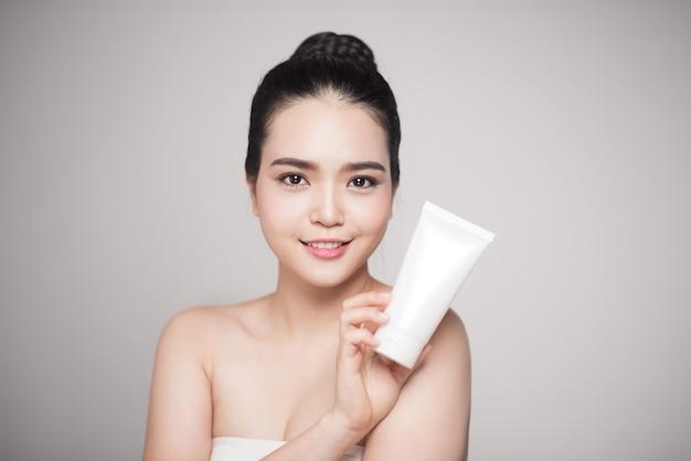 Notion de beauté. jolie femme asiatique avec une peau parfaite tenant une bouteille cosmétique