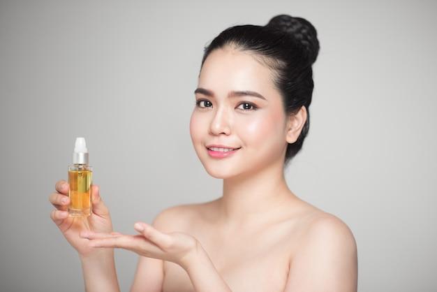 Notion de beauté. jolie femme asiatique avec une peau parfaite tenant une bouteille d'huile