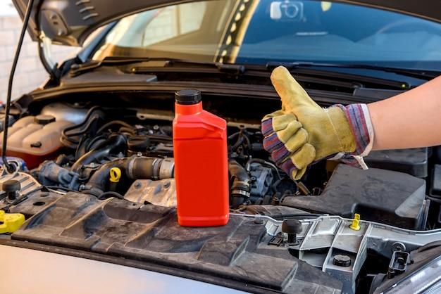 Notion de changement d'huile. main masculine dans le gant avec la bouteille d'huile et le moteur de voiture se bouchent
