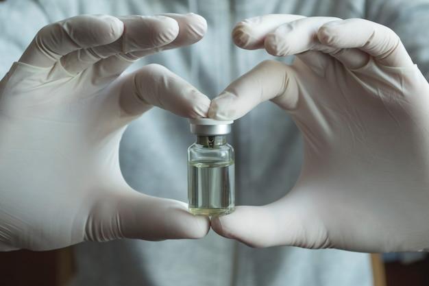 Notion de coronavirus, covid-19. un homme en gants blancs médicaux tient une bouteille de vaccin.