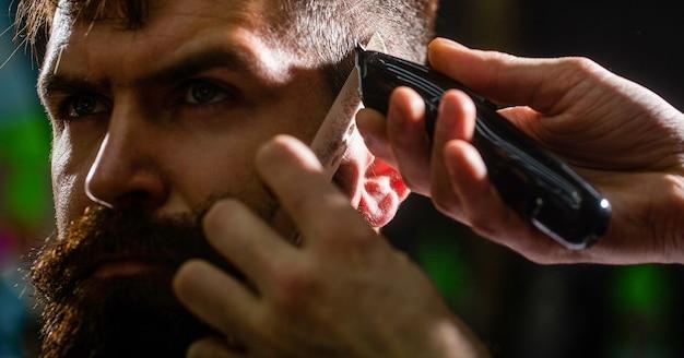 Notion de coupe de cheveux. client hipster se coupe les cheveux. homme visitant le coiffeur dans le salon de coiffure