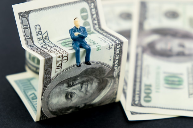 Notion de courtier financier. homme jouet assis sur un billet de banque en dollars américains.
