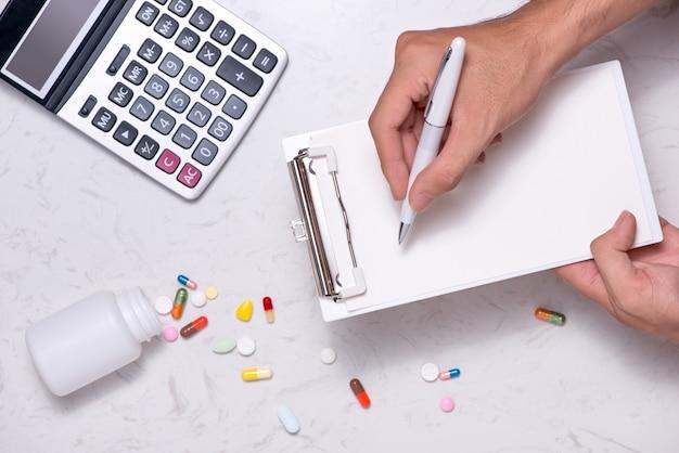 Notion de coûts de santé. flacon de médicament ouvert et capsules renversées sur la table.