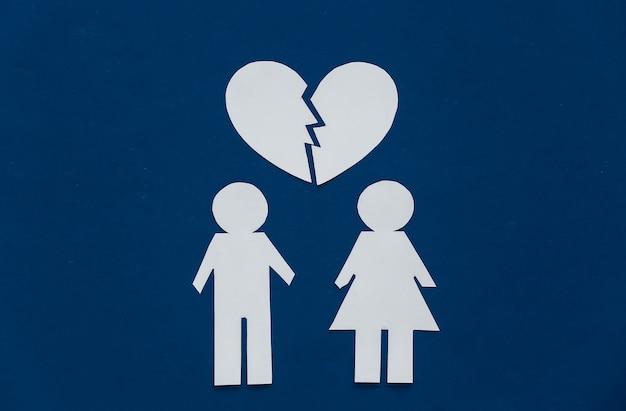 La notion de divorce. chiffres en papier de l'homme et de la femme et cœur brisé sur un bleu classique.