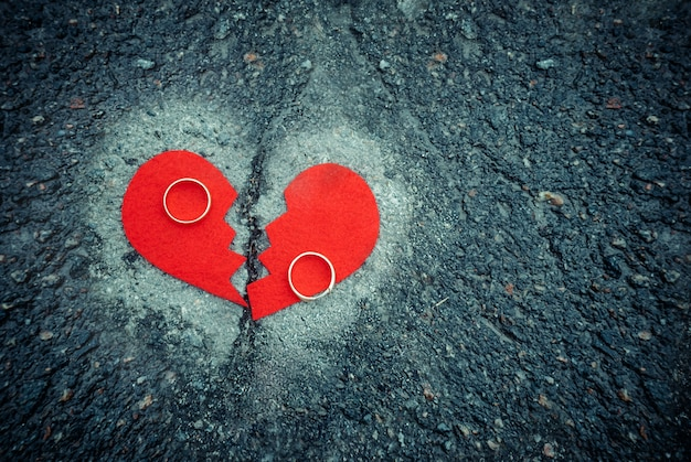 Notion de divorce - cœur brisé avec des anneaux de mariage sur l'asphalte fissuré. tonique