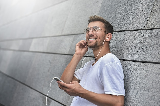 Notion d'écouteurs. personnes, technologie, voyages et tourisme - homme avec écouteurs, smartphone dans la rue de la ville et écoutant de la musique sur fond de mur gris