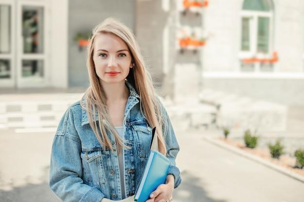 Notion d'éducation. une étudiante heureuse tient des dossiers, des cahiers, des livres dans les mains, des sourires, regardent la caméra dans le contexte d'un bâtiment universitaire moderne. espace de copie
