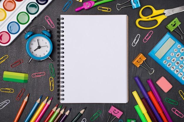 Notion d'éducation. haut au-dessus de la vue aérienne photo d'un cahier vierge entouré de papeterie multicolore isolée sur tableau noir