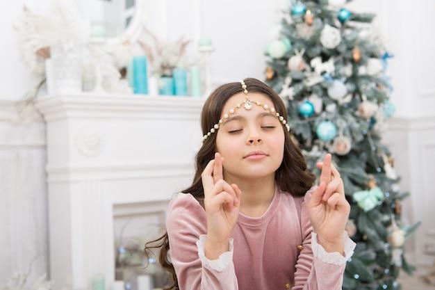 Notion d'espoir. souhait de noël de bébé rêveur. faire un vœu. en attendant le père noël. adorable fille faisant un vœu près de l'intérieur décoré d'un arbre de noël. enfant plein d'espoir. nouvel an. les rêves deviennent réalité.
