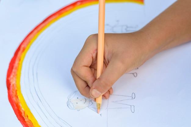 Notion de famille heureuse. enfant dessine sur une feuille de papier
