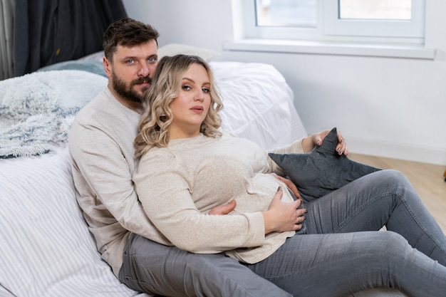 Notion de famille heureuse. mari câlin ventre femme enceinte assise étage salon intérieur près du canapé caucasien homme et femme grossesse et nouveau concept de vie. amour et soin