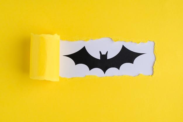 Notion d'halloween. haut au-dessus de la vue aérienne photo en gros plan de papier jaune déchiré et chauve-souris sur fond blanc avec fond