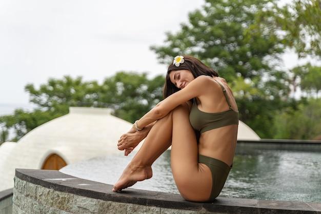 Notion de loisirs. jeune vacancier caucasienne se détendre au bord d'une piscine à débordement