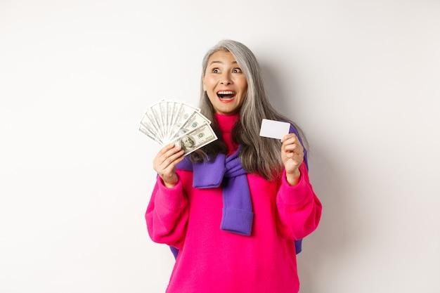 Notion de magasinage. heureuse vieille femme asiatique aux cheveux gris, l'air fascinée dans le coin supérieur gauche, montrant une carte de crédit en plastique et des dollars en argent, fond blanc.