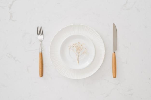 Notion de manger. cuillère, fourchette et plat blanc sur fond de pierre blanche.