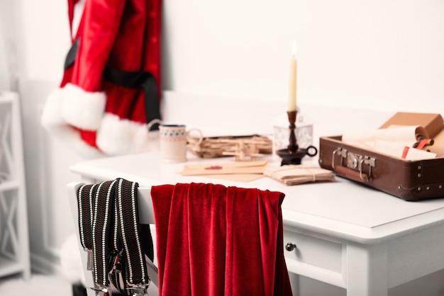 Notion de noël. costume de père noël suspendu dans une salle blanche. coffre avec listes de souhaits sur la table, gros plan