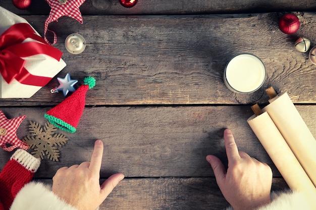 Notion de noël. mains du père noël, coffret cadeau, jouets, verre de lait sur table en bois, gros plan