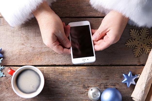 Notion de noël. santa prend le téléphone intelligent dans les mains sur une table en bois, gros plan
