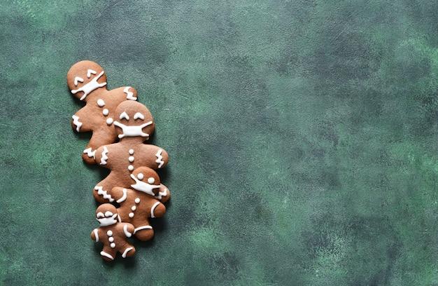 Notion de nouvel an. famille de pain d'épice en masques sur fond de béton vert. vue d'en-haut.