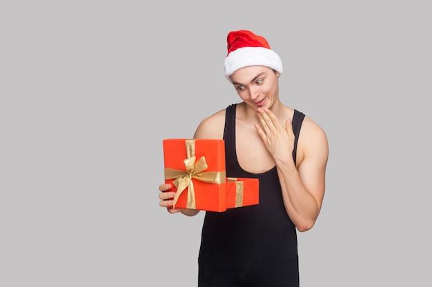 Notion de nouvel an. homme au chapeau rouge tenant une boîte cadeau rouge et regardant à l'intérieur avec une drôle de tête étonnée. intérieur, tourné en studio, isolé sur fond gris