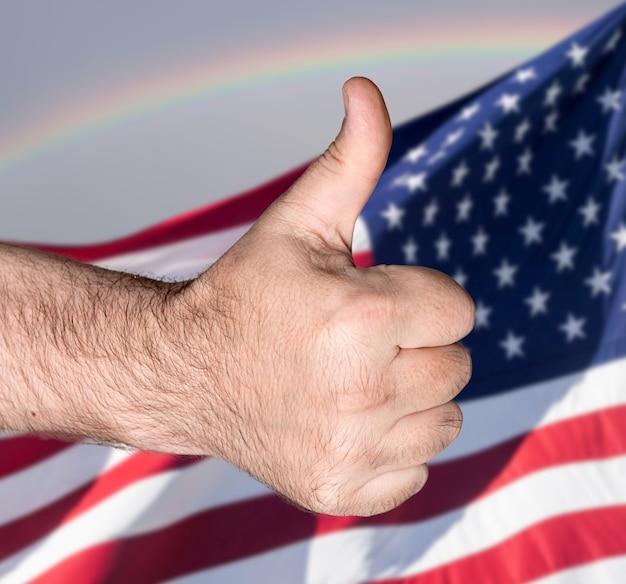 Notion patriotique. le pouce en l'air contre le drapeau des états-unis d'amérique
