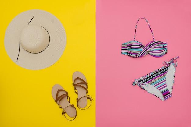 Notion de plage. chapeau femme, sandales, maillot de bain. jaune avec fond rose, vue de dessus