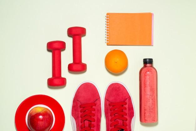 Notion de remise en forme. baskets, pomme, haltère et bouteille de jus de fruits sur fond de couleur pastel.