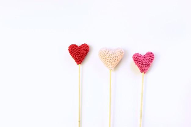 Notion de saint-valentin. trois coeur tricoté sur fond blanc.