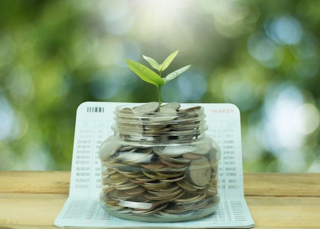 Notion de sauver et de l'argent, empilés de pièces de monnaie avec jeune arbre grandir sur des bocaux et des banques de livres