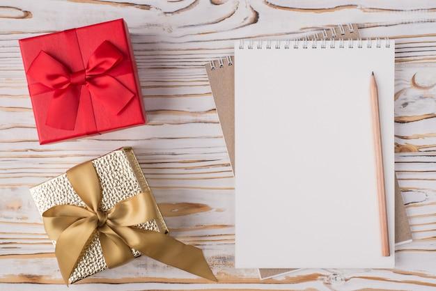 Notion de vacances de noël. en haut au-dessus de la vue aérienne, photo à plat d'un crayon de cahier vierge et de petits cadeaux isolés sur un fond en bois clair avec fond