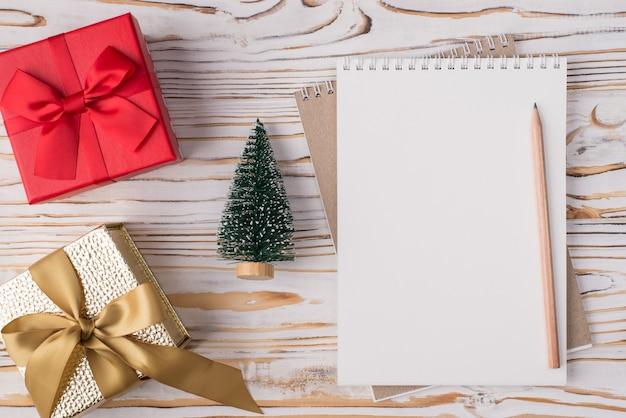 Notion de vacances de noël. en haut au-dessus de la vue aérienne, photo à plat d'un crayon pour ordinateur portable vierge de petits cadeaux et d'un arbre de noël isolé sur un fond en bois clair avec fond