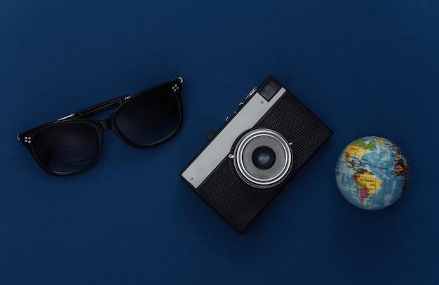 Notion de voyage. appareil photo et globe, lunettes de soleil sur fond bleu classique. couleur 2020. vue de dessus.