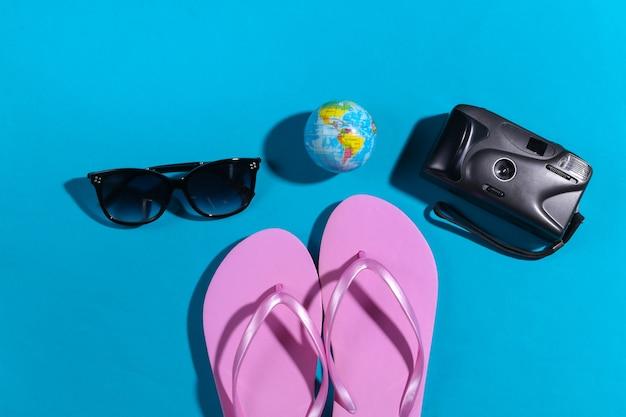 Notion de voyage. appareil photo, globe, lunettes de soleil, tongs sur fond bleu avec ombre. vue de dessus