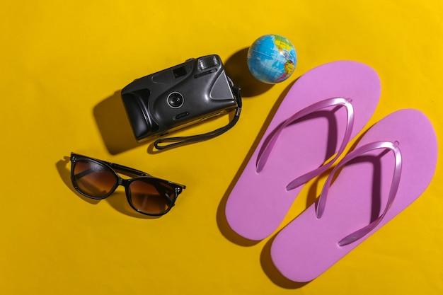 Notion de voyage. appareil photo, globe, lunettes de soleil, tongs sur fond jaune avec ombre. vue de dessus
