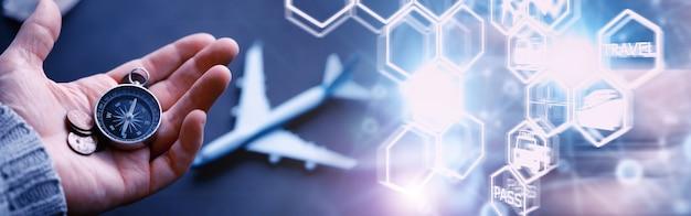 Notion de voyage. boussole magnétique dans la main. navigateur rétro en main une carte et un fond d'avion. fond d'aventure.