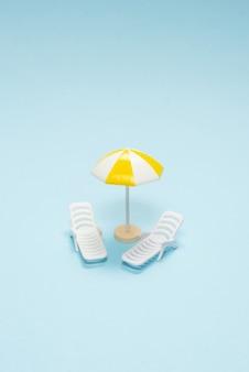 Notion de voyage. chaise longue, parasol jaune sur fond bleu. espace de copie.