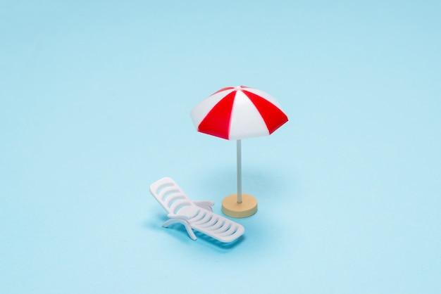Notion de voyage. chaise longue, parasol rouge sur fond bleu. espace de copie.