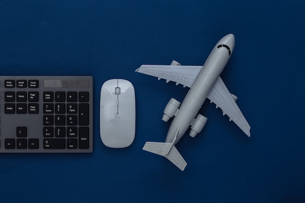 Notion de voyage. clavier de pc et avion sur un bleu classique