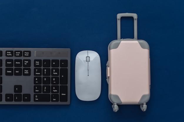 Notion de voyage. clavier pc et mini bagage de voyage sur un bleu classique