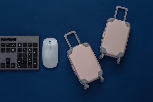Notion de voyage. clavier pc et mini bagages de voyage sur un bleu classique