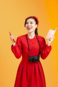 Notion de voyage. jeune femme asiatique heureuse tenant un passeport avec des billets d'avion, isolée sur fond orange