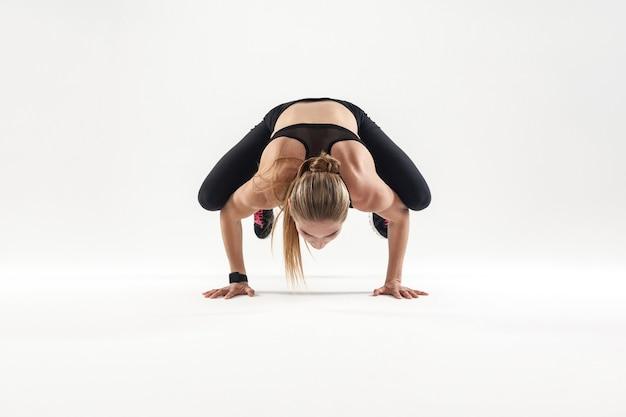Notion de yoga. posture de bakasana. femme forte faisant du yoga. studio tourné sur fond gris